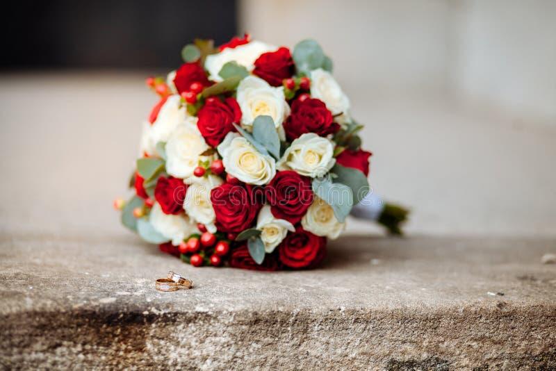 Närbild av vigselringar på bakgrundsbröllopbukett av rosor av bär och gräsplaner med lavendel royaltyfri foto