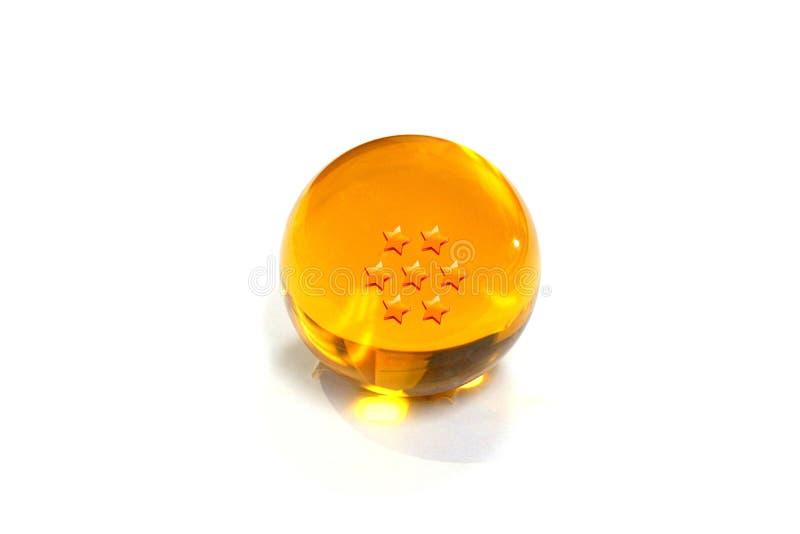 Närbild Crystal Ball som är gul med stjärna sju på en vit bakgrund royaltyfria bilder
