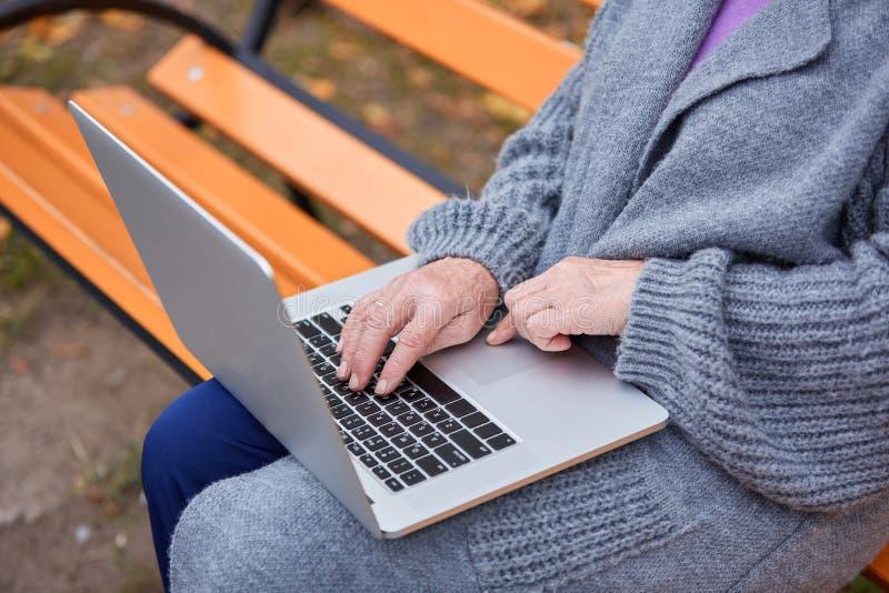 Närbild Den vuxna kvinnan med ett bärbar datorsammanträde på en bänk i en höst parkerar royaltyfri foto
