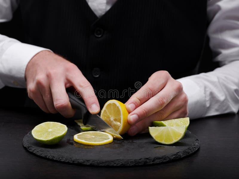 Närbild en bartender som klipper en citron En man som skivar den gula citronen på en svart bakgrund Begrepp för fruktsmoothiedana royaltyfria foton