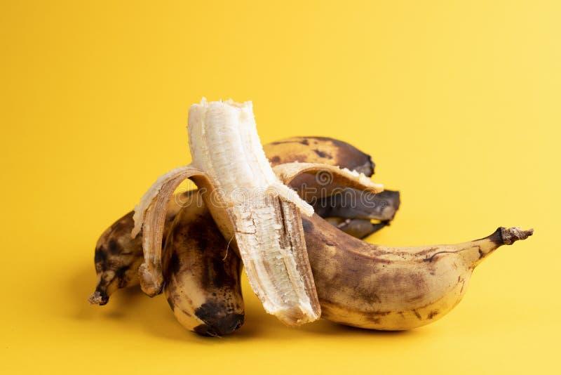 Närbild en skalade bananen och två unpeeled övermogna svärtade fula bananer på gul bakgrund royaltyfri bild