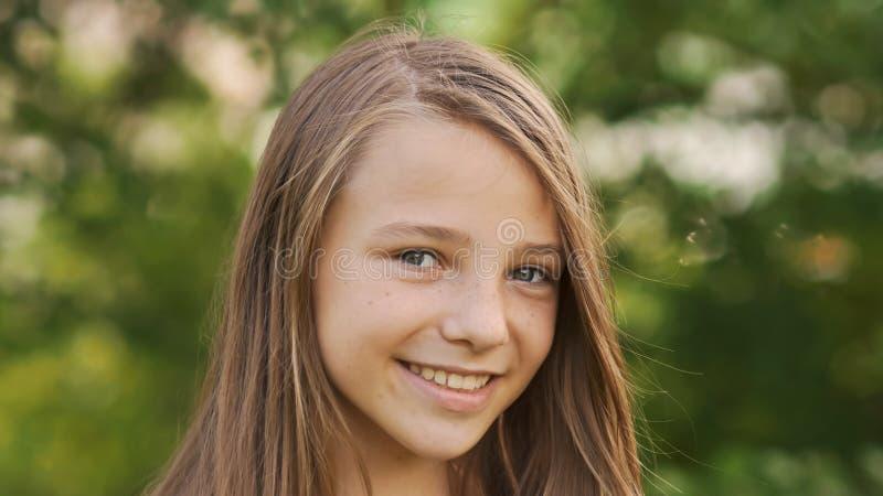 Närbild för flickatonåringframsida med generade fräknar och roligt posera och att spela med hans hår arkivbilder