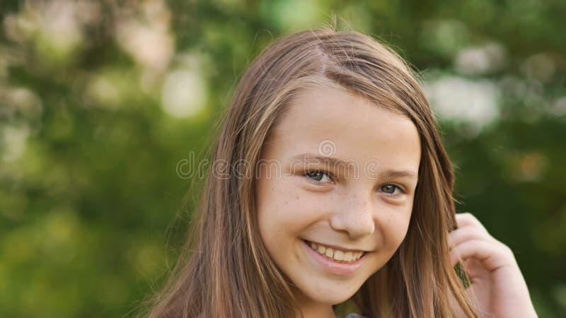 Närbild för flickatonåringframsida med generade fräknar och roligt posera och att spela med hans hår royaltyfri fotografi