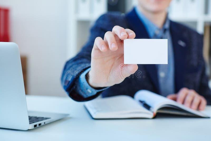 Närbild för kort för affärsmaninnehavbesök Kort för affär för manvisningmellanrum Person i blåttdräkt Övre design för åtlöje royaltyfri fotografi