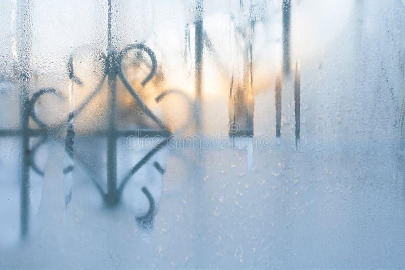 Närbild fryst vinterfönster som töar litet från morgonsolen arkivfoto