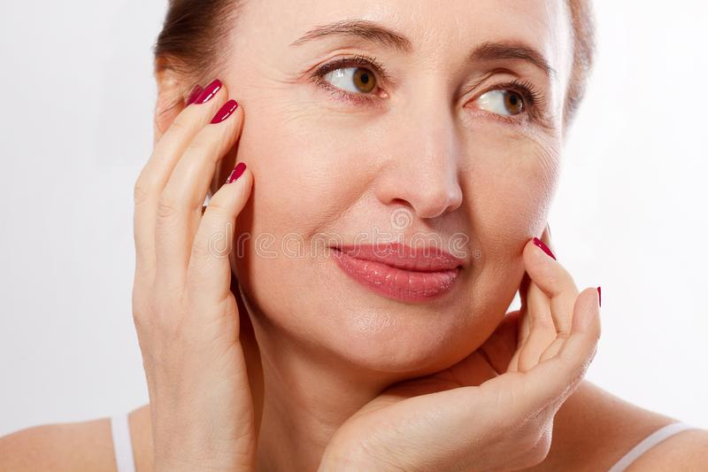 Närbild och makrostående av den härliga och sunda mitt åldras kvinnaframsida på vit bakgrund Skrynklor och klimakterium arkivfoto