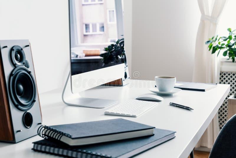 Närbild på böcker, högtalare och den skrivbords- datoren på skrivbordet i den vita inre för freelancer` s Verkligt foto royaltyfri bild