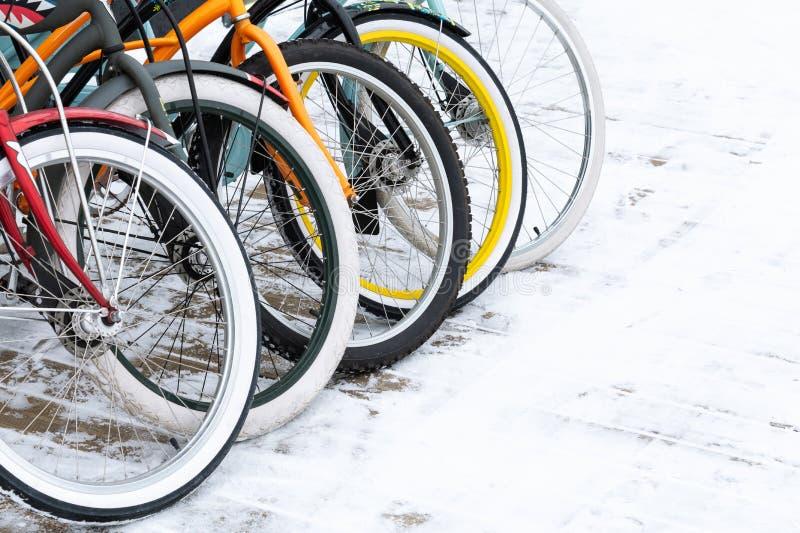 Närbild på de ljusa hjulen av cyklar som står på snön royaltyfri bild