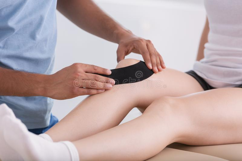 Närbild på doktorn som sätter bandet på patients ben under utbildning royaltyfri foto