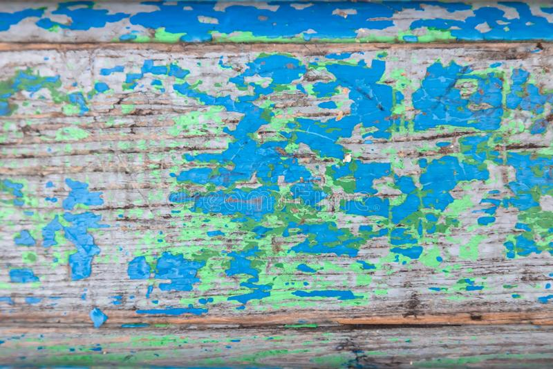 Närbild på en träplan yttersida med gammal skalande målarfärg av olika färger med sprickor på tre bräden red f?r bl? green arkivfoton
