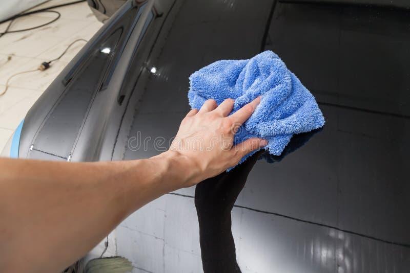 Närbild på handen av ett manligt rengöringsmedel med en blå microfibertorkduk som torkar en svart bil, når tvätt och det har appl arkivfoton