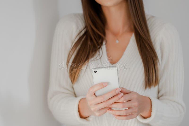 Närbild på kvinnahänder genom att använda en smartphone arkivbild