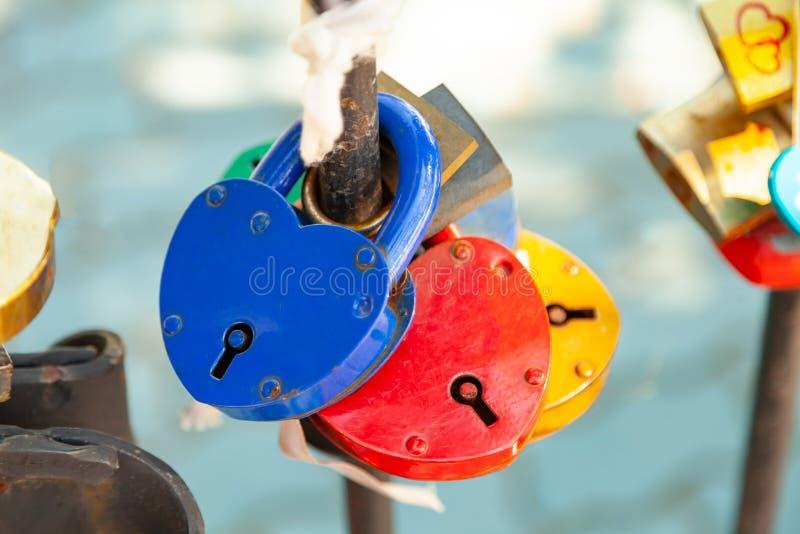 Närbild på lås av hjärtor i olika färger och former som hänger på staketet som ett tecken av evig förälskelse, som hängs under royaltyfria foton