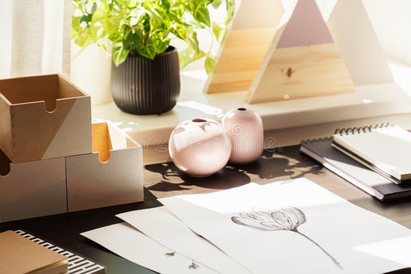 Närbild på skrivbordet med teckningar och träaskar i workspaceinre med växten arkivfoto