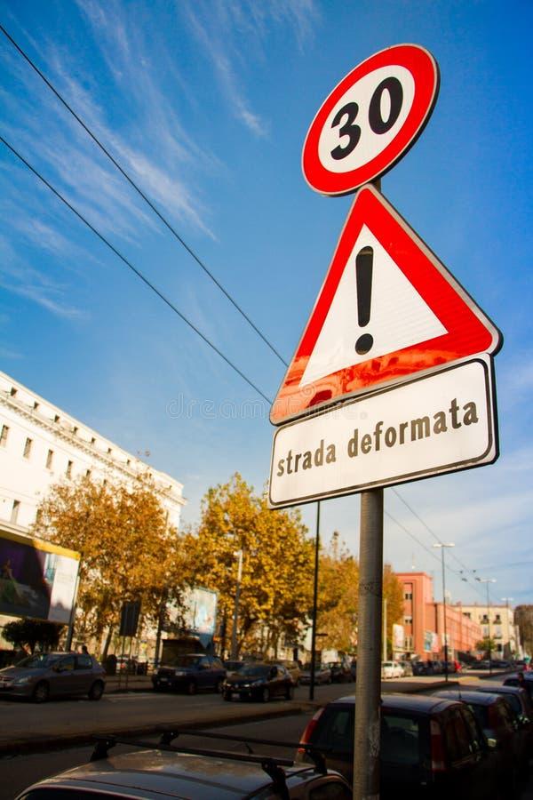 Närbild på vägmärken för en pol om hastighetsbegränsningen till trettio och ett tecken av tilldragning av uppmärksamhet på vägen  fotografering för bildbyråer