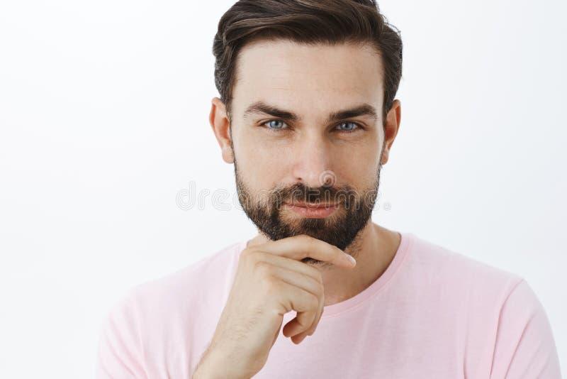 Närbild som skjutas av den förtjusta karismatiska och stiliga macho mannen med skägget och blåa ögon som sensually skelar på kame fotografering för bildbyråer