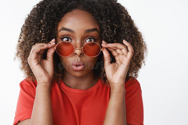 Närbild som skjutas av förvånad och road attraktiv kvinnlig afrikansk amerikanflicka med lockigt hår som av tar solglasögon arkivfoto
