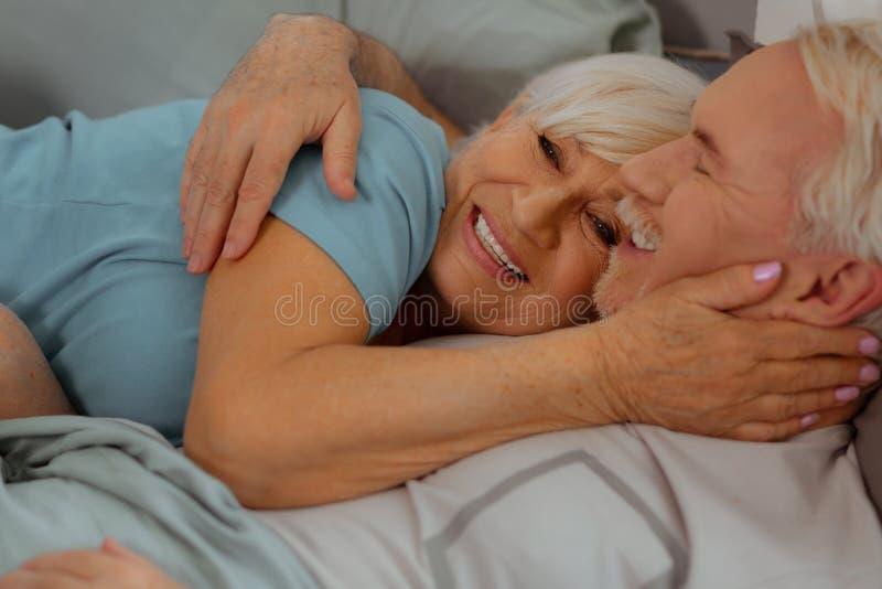 Närbild som skjutas av maker som kramar och ligger i sängen arkivfoton