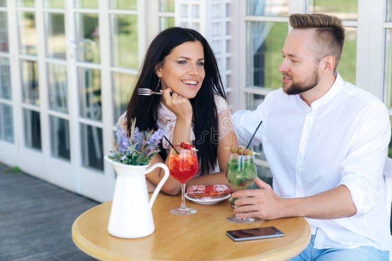 Närbild stående av vänner En man och en kvinna sitter i ett kafé, talar och har en bra tid flickaparkleenden går arkivfoton