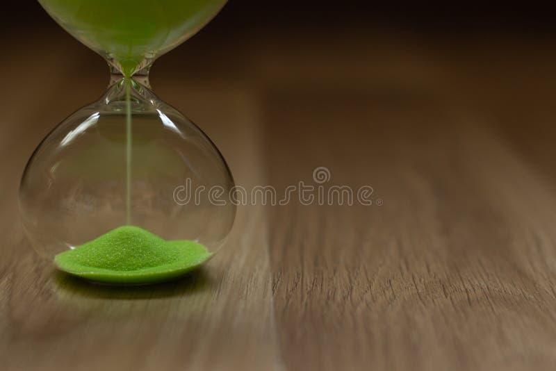 Närbild timglas med grön sand på en träbakgrund arkivbilder