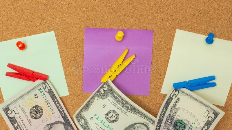 Närbild tre färgrika anmärkningar med häftstift och klädnypor med dollar som isoleras på en korkbakgrund royaltyfri bild