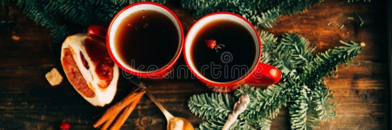 Närbild två glass koppar som är fulla av varmt, rött aromatiskt citronte med mörk choklad på en sörjafilial och en tabellbakgrund arkivbild