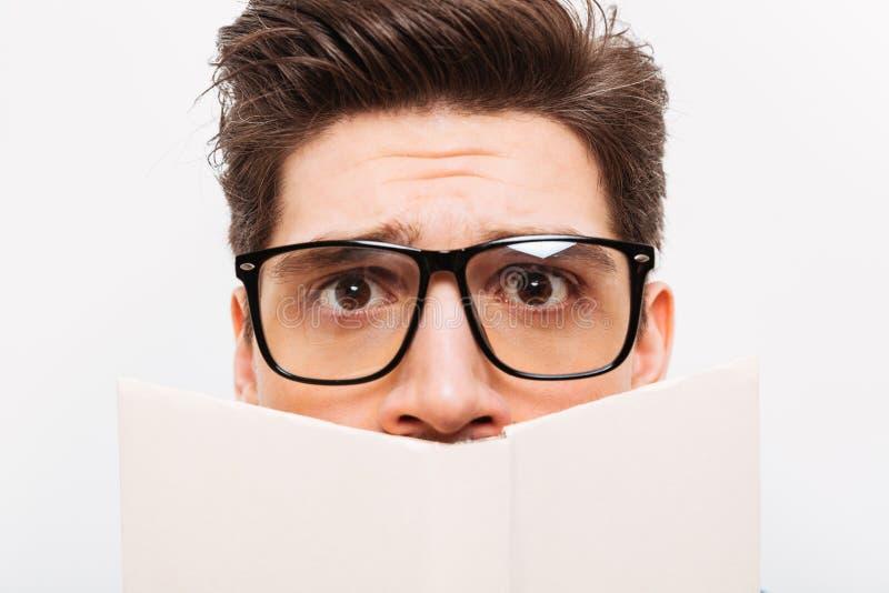 Närbildbild av den förvirrade nerden i glasögon som döljer bak boken arkivfoton