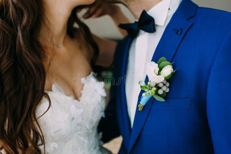 Närbildbild av en Boutonniere på omslaget för brudgum` s Den suddiga bruden och brudgummen är kyssande artistically arkivbilder