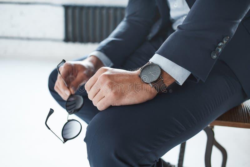 Närbildbild av en stilfull affärsman som sitter på stolen med den märkta klockan på hans hand och rymmer exponeringsglas royaltyfri fotografi