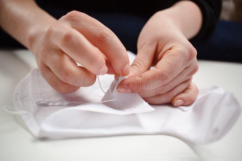Närbildbild av händerna av en sömmerska på arbete med vitt tyg fotografering för bildbyråer