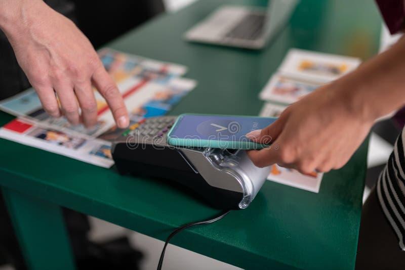Närbildbild av kvinnan som betalar genom att använda PayPass på telefonen arkivbilder