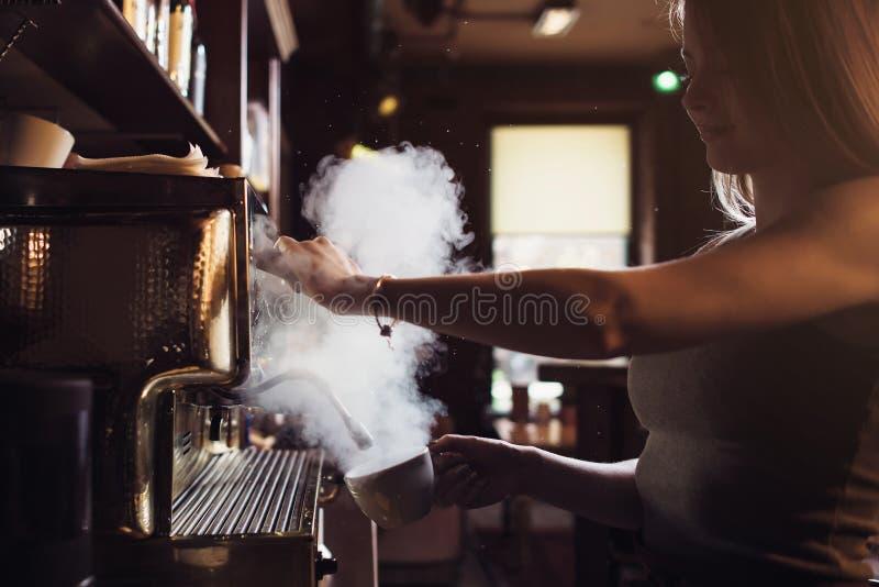 Närbildbilden av den kvinnliga baristaen genom att använda dendanande maskinen för att ånga mjölkar i kafé royaltyfria foton