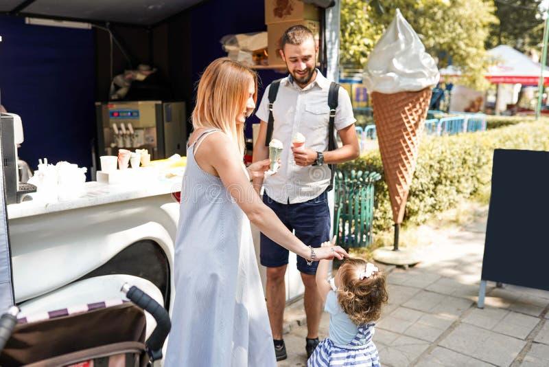 Närbildbilden av en ung lycklig familj som spenderar deras helg i, parkerar och äter glass royaltyfri foto