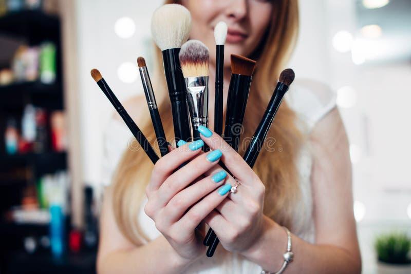 Närbildbilden av kvinnlign räcker att rymma en uppsättning av sminkborstar royaltyfria foton