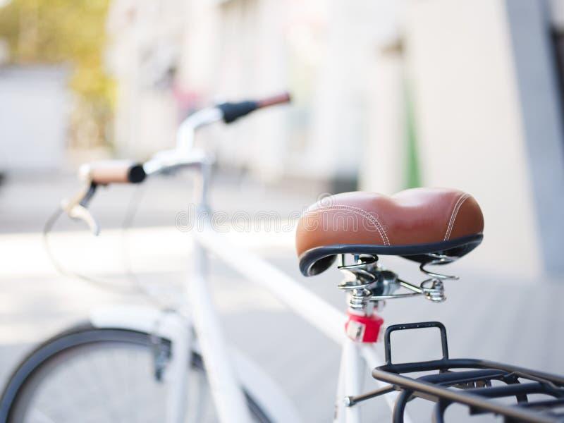Närbildcykelplats på en suddig bakgrund Brunt retro cykelplats Modern transport kopiera avstånd royaltyfri fotografi