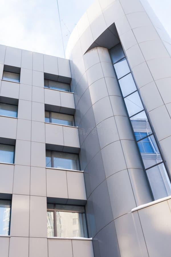 Närbilddel av ljus - grå modern byggnad med glass fönster royaltyfri foto