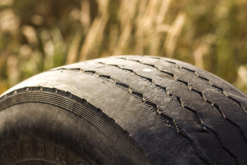 Närbilddetalj av gummihjulet för bilhjul som dåligt är slitet och som är skalligt på grund av fattig spårning eller justeringen a royaltyfria foton