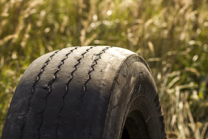 Närbilddetalj av gummihjulet för bilhjul som dåligt är slitet och som är skalligt på grund av fattig spårning eller justeringen a royaltyfri bild