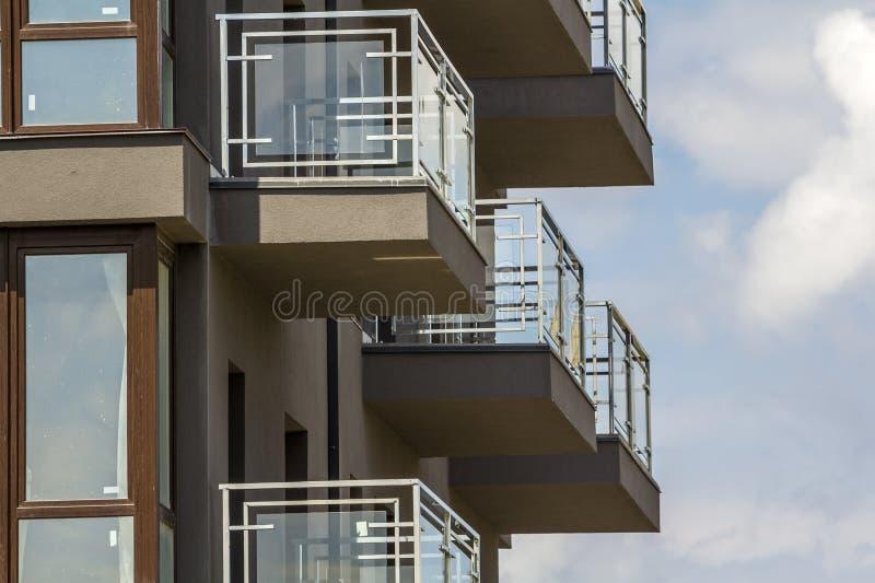 Närbilddetalj av hyreshusväggen med balkonger och skinande fönster på bakgrund för blå himmel royaltyfri bild