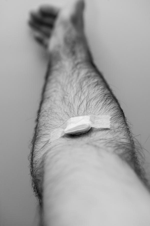 Närbilddetalj av manhanden med tejpen efter blodtrans. arkivbild