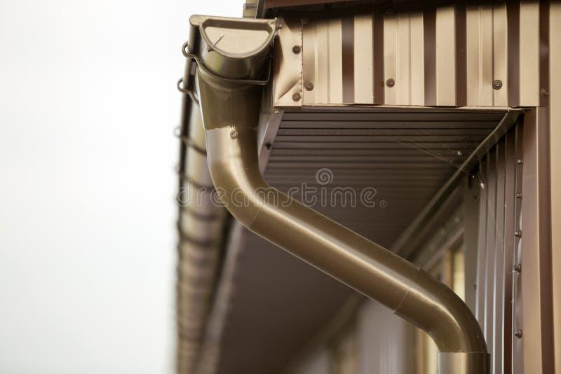 Närbilddetalj av stugahushörnet med sid för metallplankor och taket med avloppsrännaregnsystemet arkivfoto