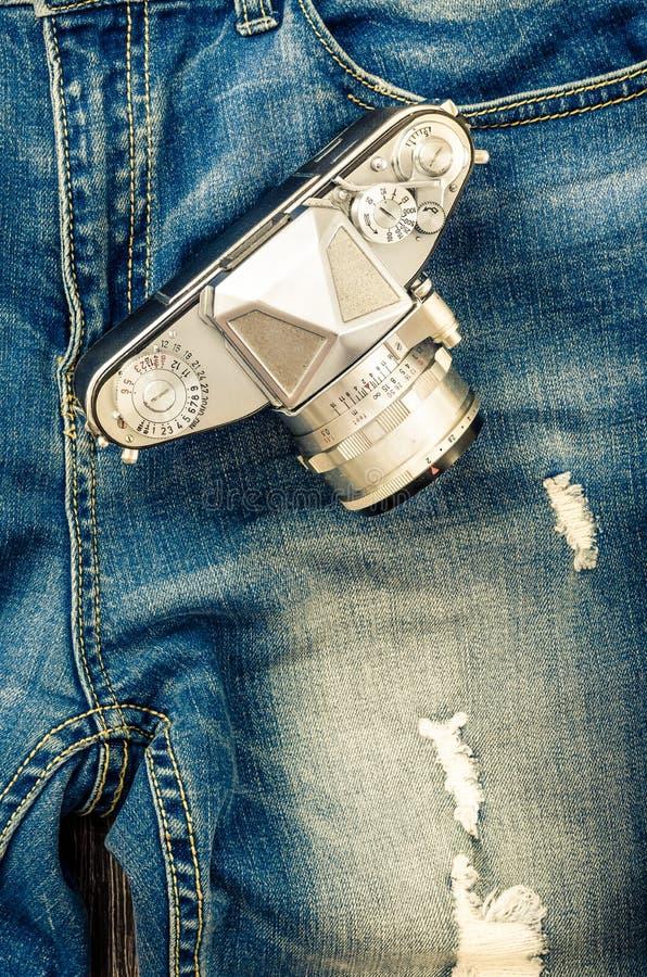 Närbilddetalj av tappningjeans med den klassiska kameran royaltyfria foton