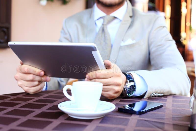 Närbilden av affärsmannen räcker den rörande digitala minnestavlan arkivfoto