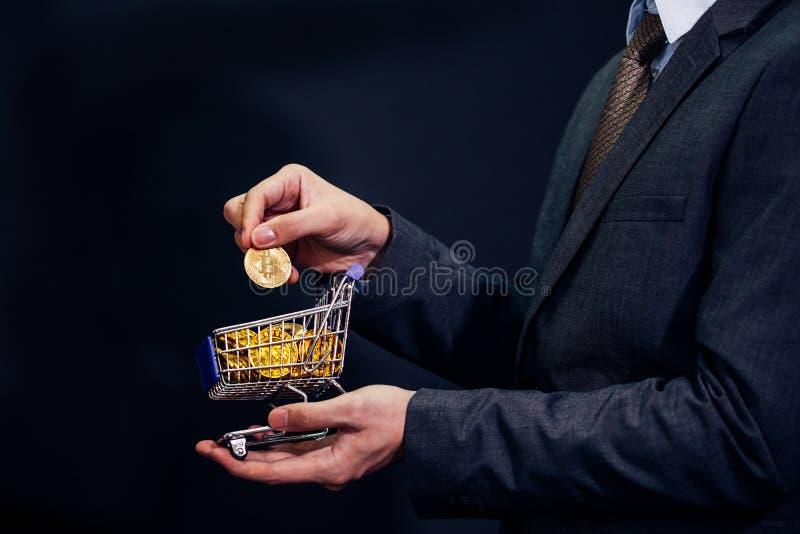 Närbilden av affärsmanvisningen och innehavet skjuter vagnen mycket av bitcointecknet av myntet arkivbilder