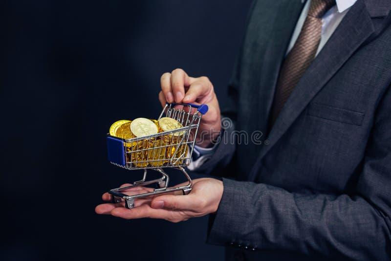 Närbilden av affärsmanvisningen och innehavet skjuter vagnen mycket av bitcointecknet av myntet - cryptocurrencyen och framtid av arkivfoto