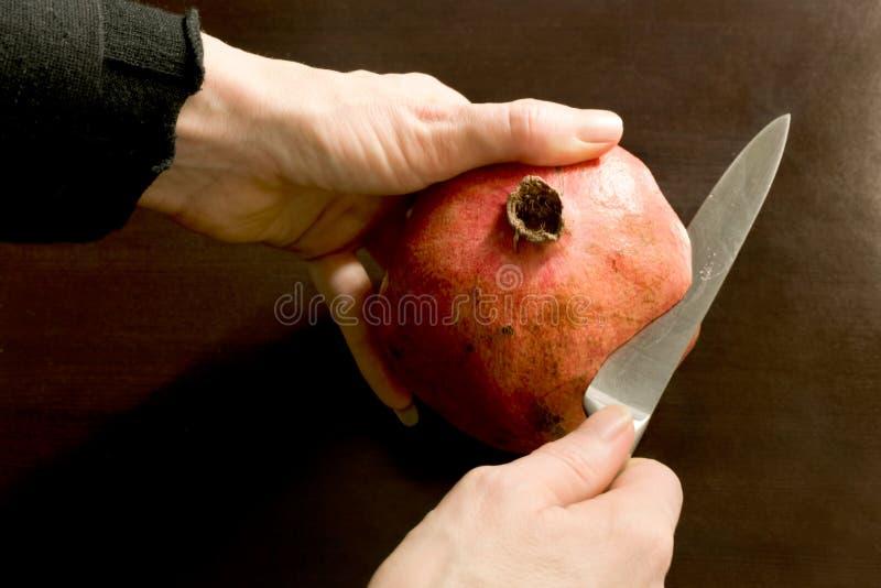 Närbilden av att klippa för händer öppnar en granatäpple med en rostfritt stålkniv - mörk bakgrund royaltyfri fotografi