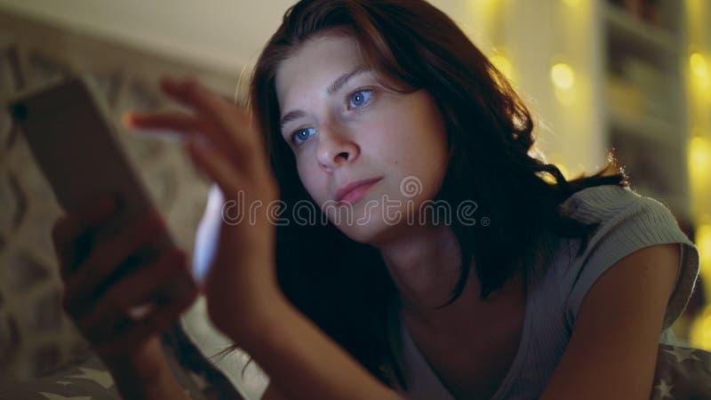 Närbilden av barn koncentrerade kvinnan som använder smartphonen som hemma ligger i säng på natten arkivfoto