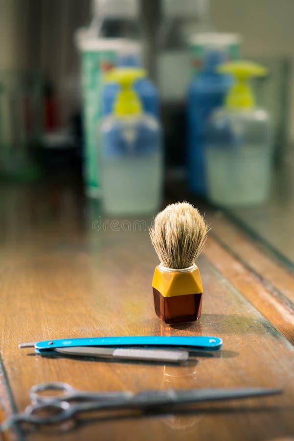Närbilden av borsten och rakkniven i barberare shoppar royaltyfria foton