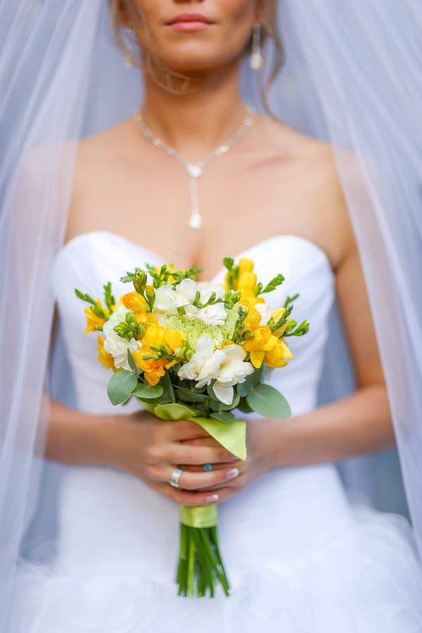 Närbilden av bruden räcker den hållande härliga bröllopbuketten arkivbild
