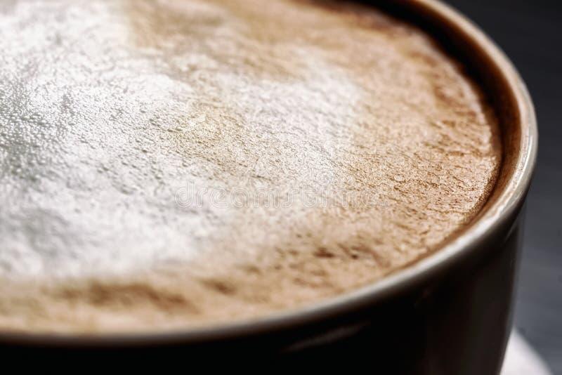 Närbilden av delen av mörker rånar med smaklig kaffeespresso och mjukt skum royaltyfri fotografi
